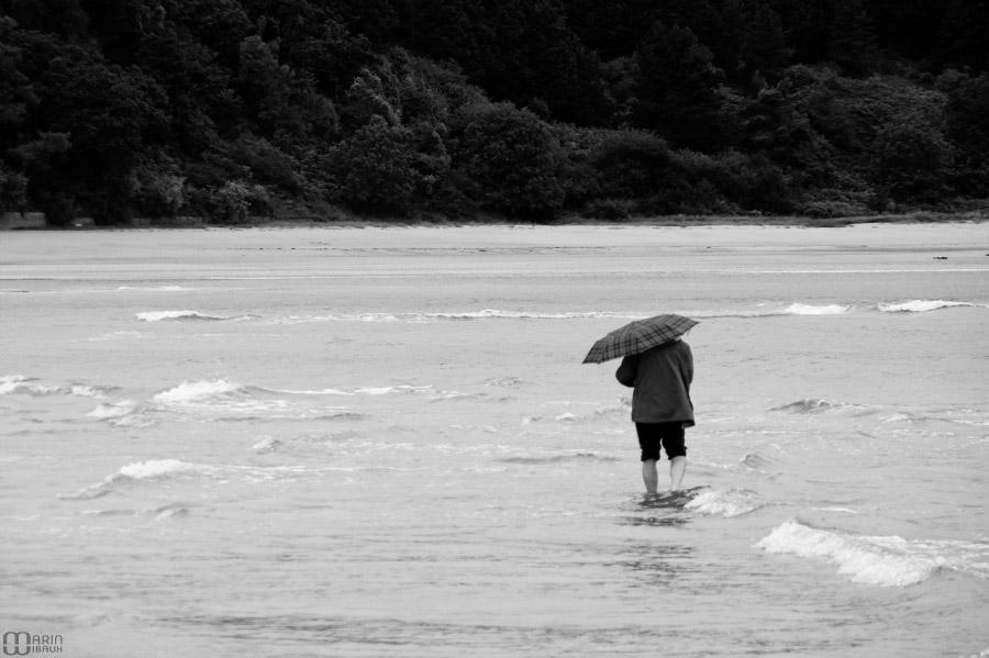 Homme en parapluie en bord de mer