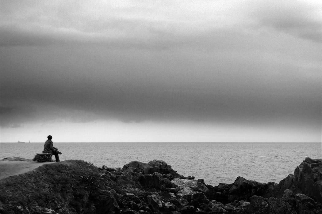 Homme seul sur un banc en bord de mer regardant l'horizon - photo noir et blanc