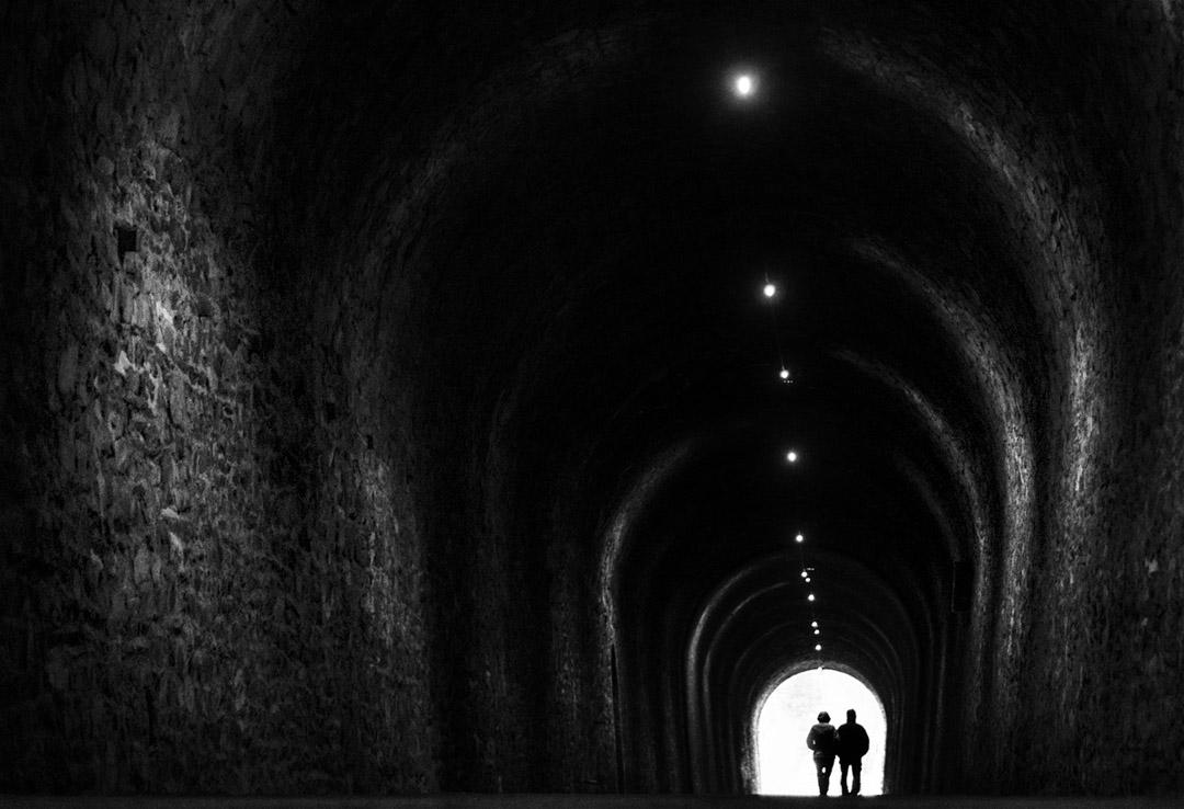Noir et blanc : couple sortant d'un tunnel, anciennement de chemin de fer