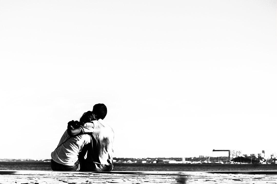 Couple amoureux assis sur le quai face au Tage à Lisbonne : photo noir et blanc