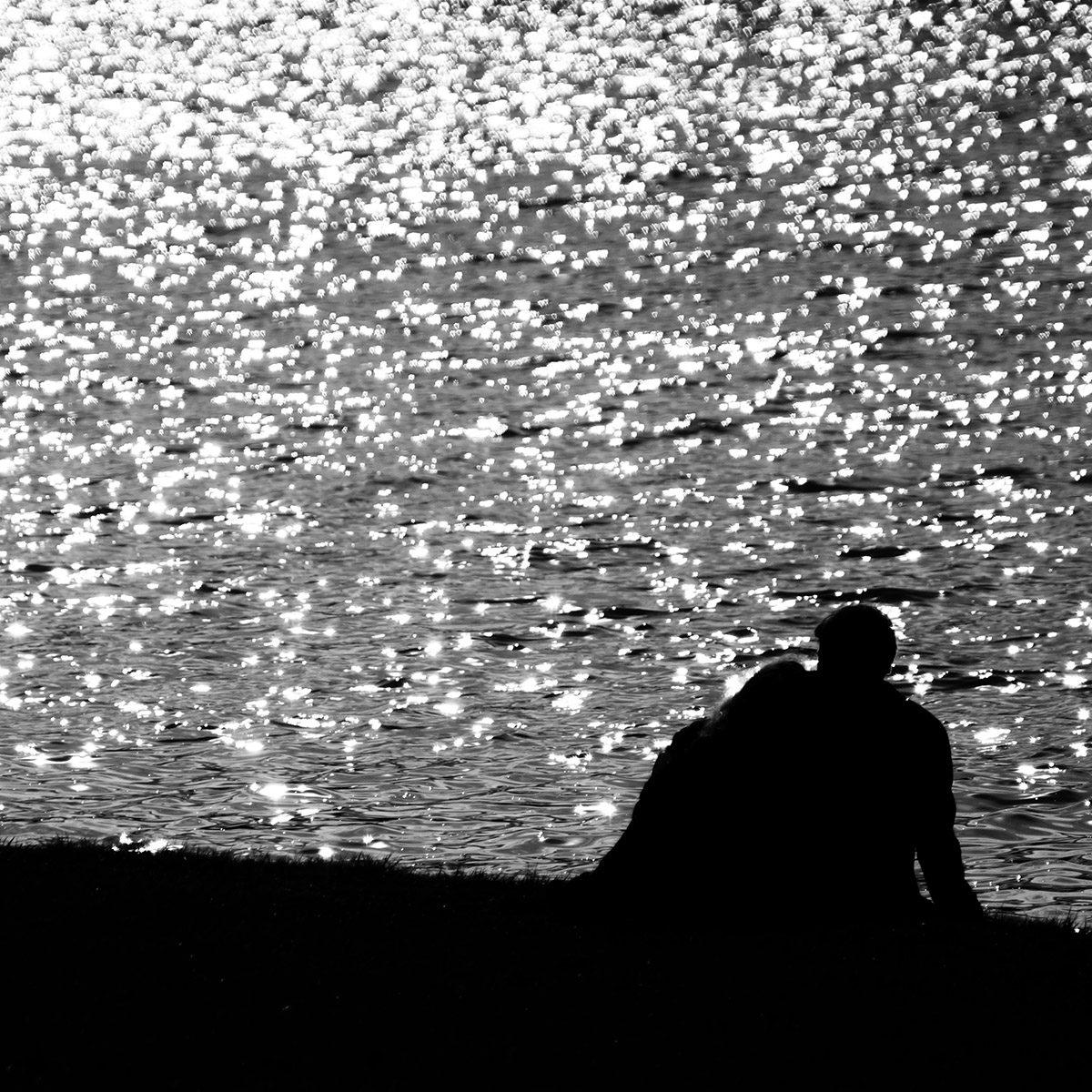 Couple amoureux face aux miroitements du canal du château de Versailles ; silhouette en noir et blanc