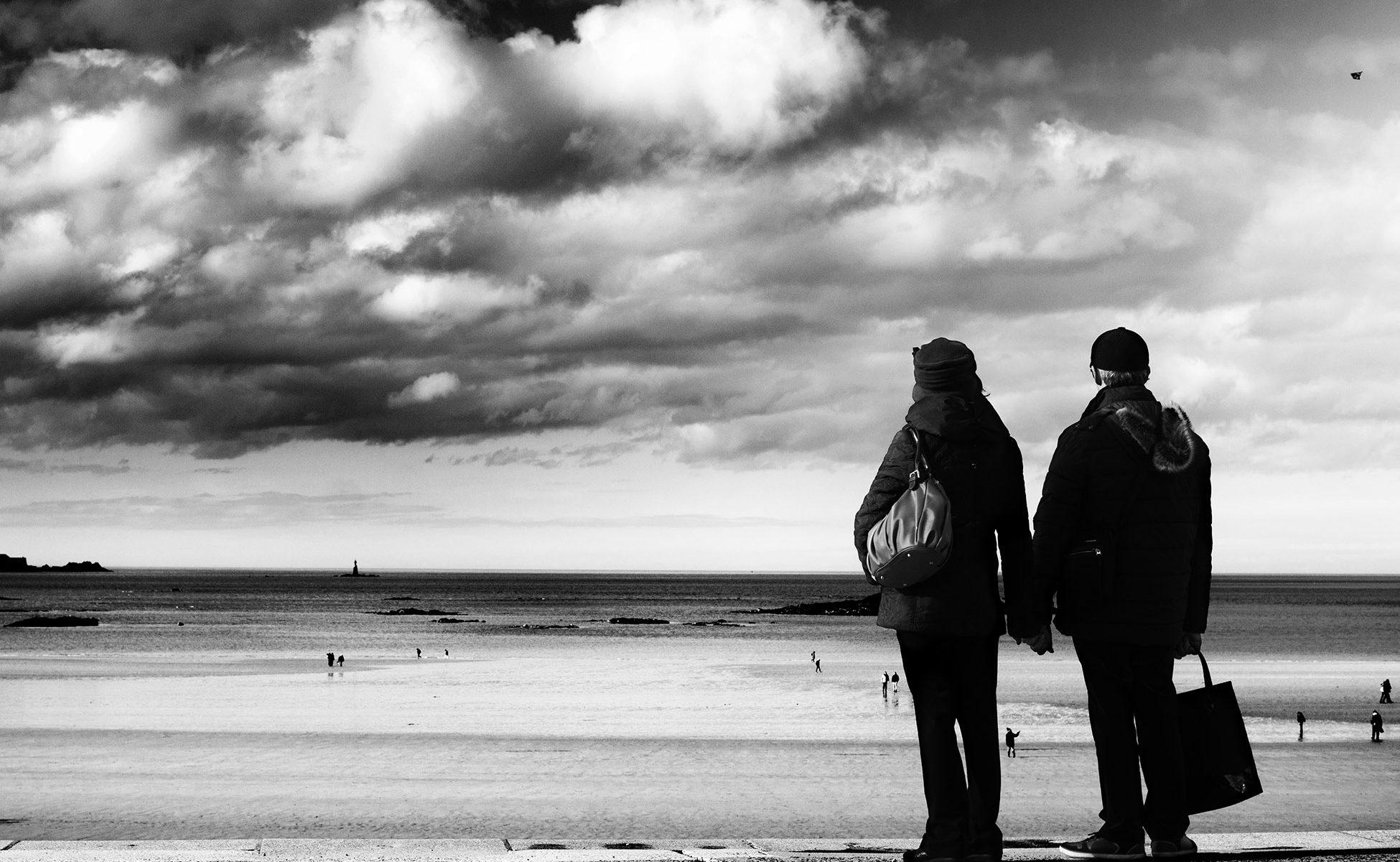 Couple qui regarde un enfant jouer au cerf-volant sur la plage du Sillon de Saint-Malo - noir et blanc et ciel nuageux
