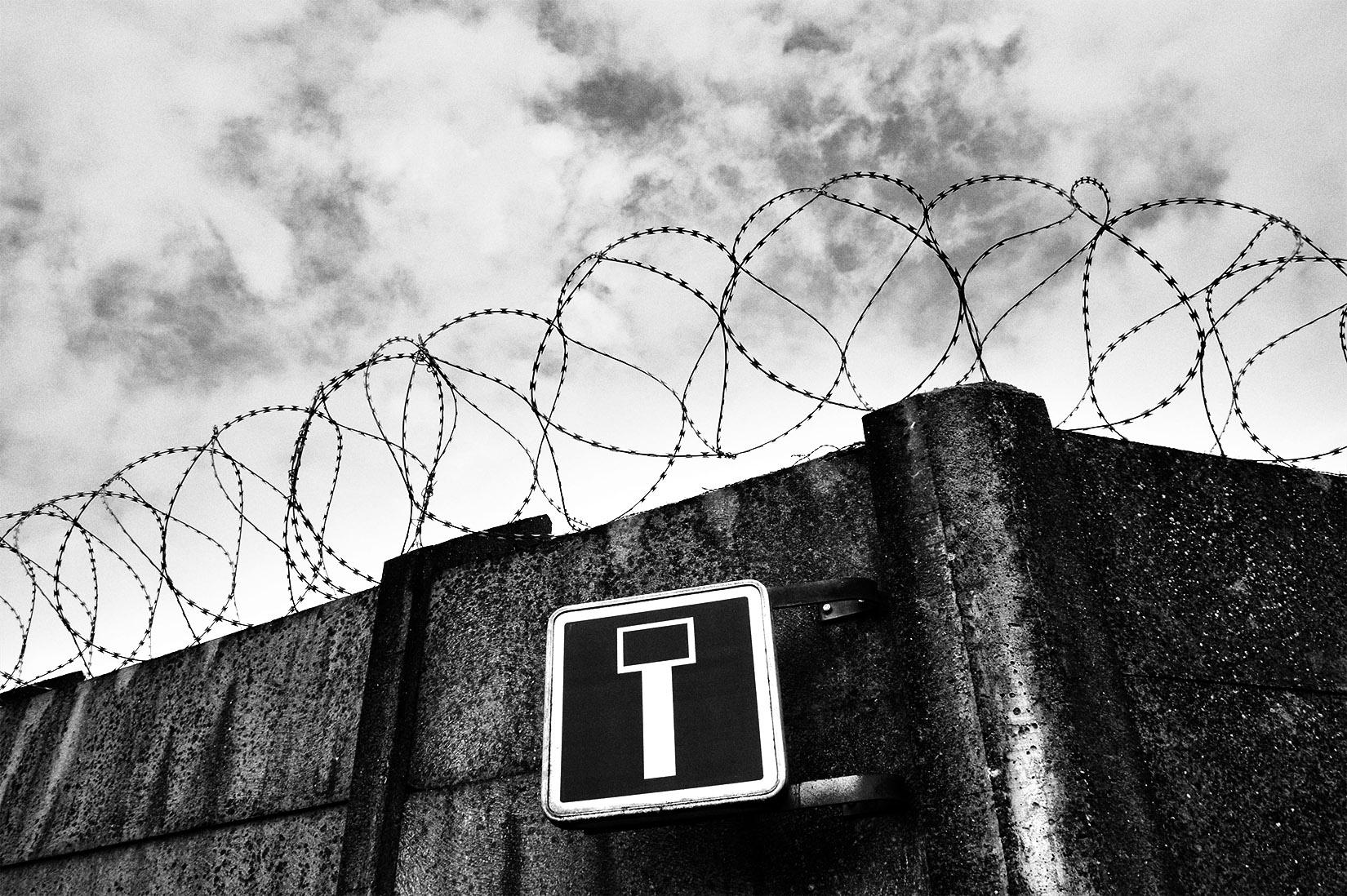 mur et fil de fer barbelé dans une impasse ; noir et blanc