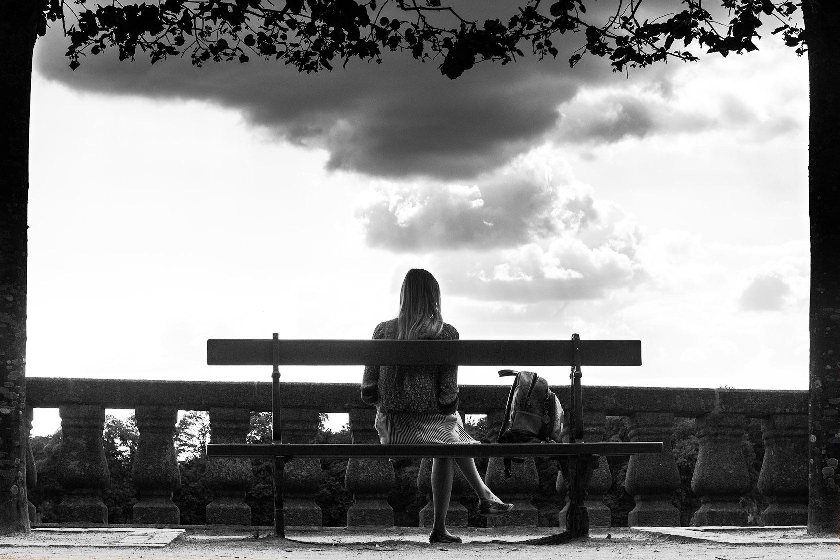 Portrait de dos : femme assise sous les nuages