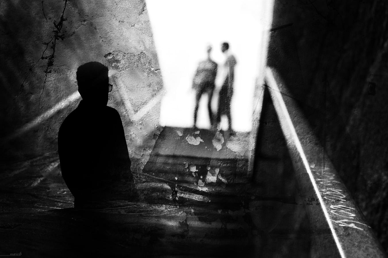 silhouette d'un homme observe en contre-jour un couple