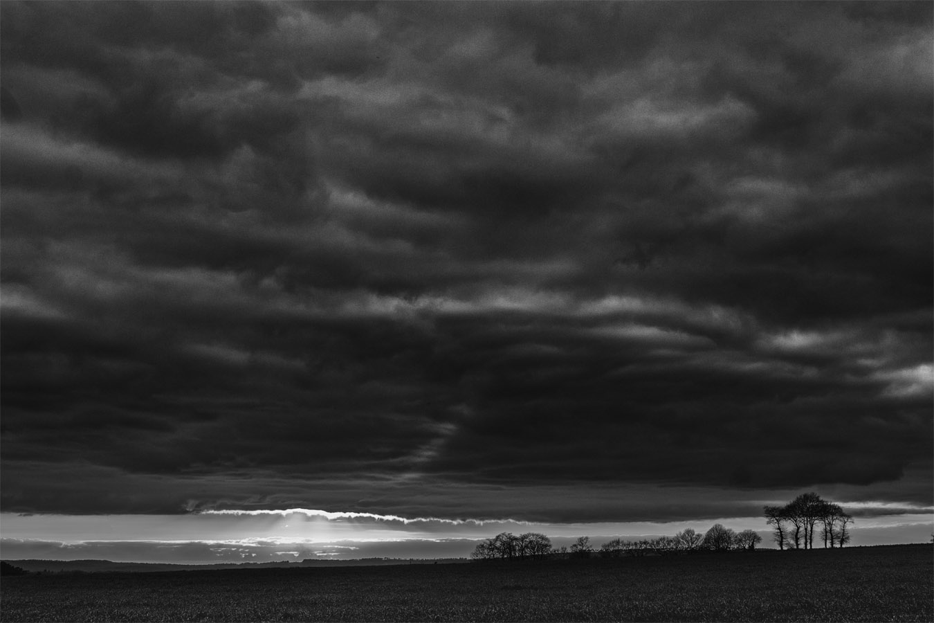 Coucher de soleil avec ciel chargé de nuages ; noir et blanc