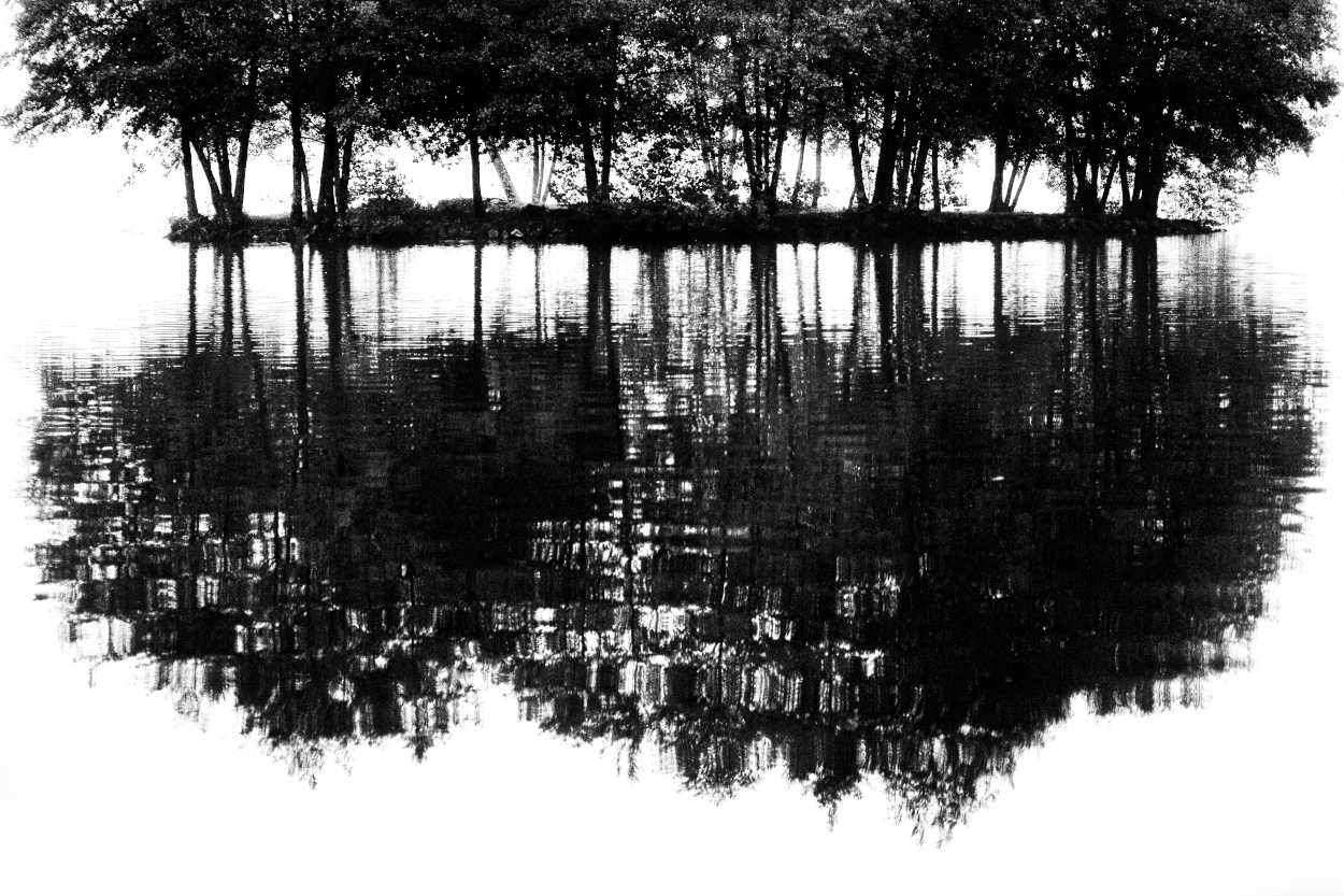 Reflet d'un îlot sur l'eau d'un étang