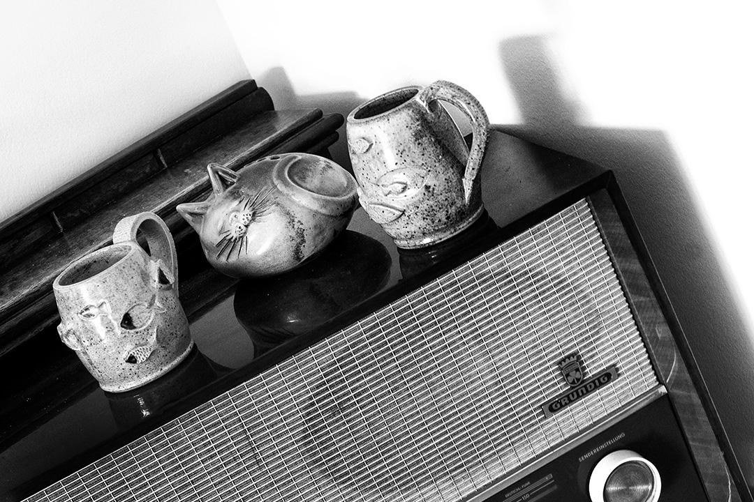 Bibelots : 1 chat endormi entre deux tasses de terre cuite avec des poissons incrustés : le rêve de Grundig, le chat qui dort sur une radio vintage