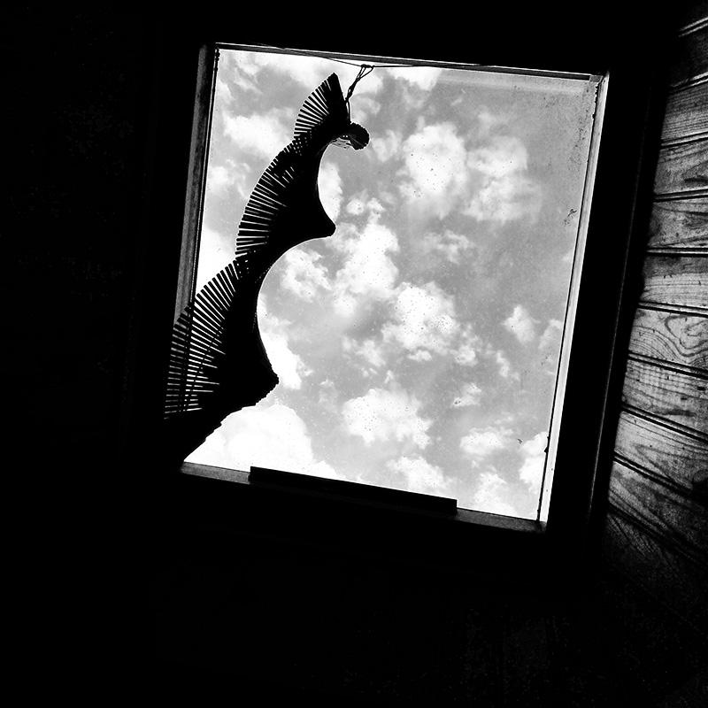 Lucarne de grnier donnant sur un ciel entre nuage et soleil