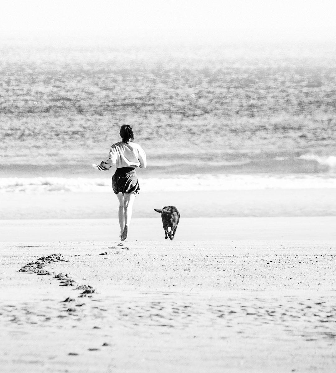 Jeune fille qui, sandalles à la main, court vers la mer accompagnée de son chien