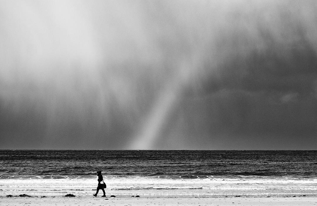 Femme qui marche l long du bord de mer sous un arc en ciel