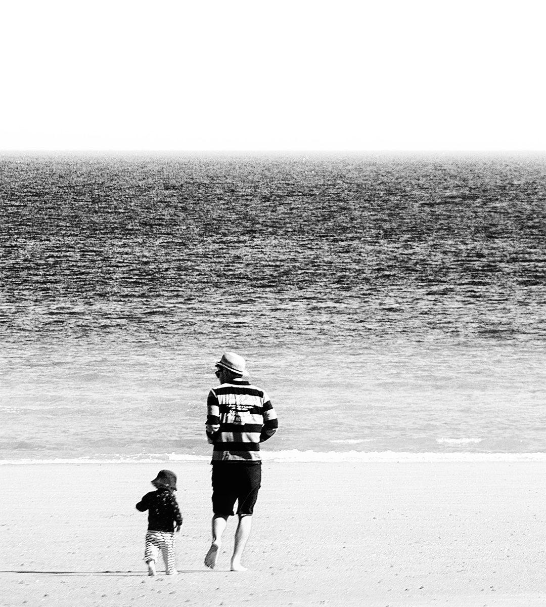 Un père et son enfant courent ensemble sur le sable de la plage vers la mer