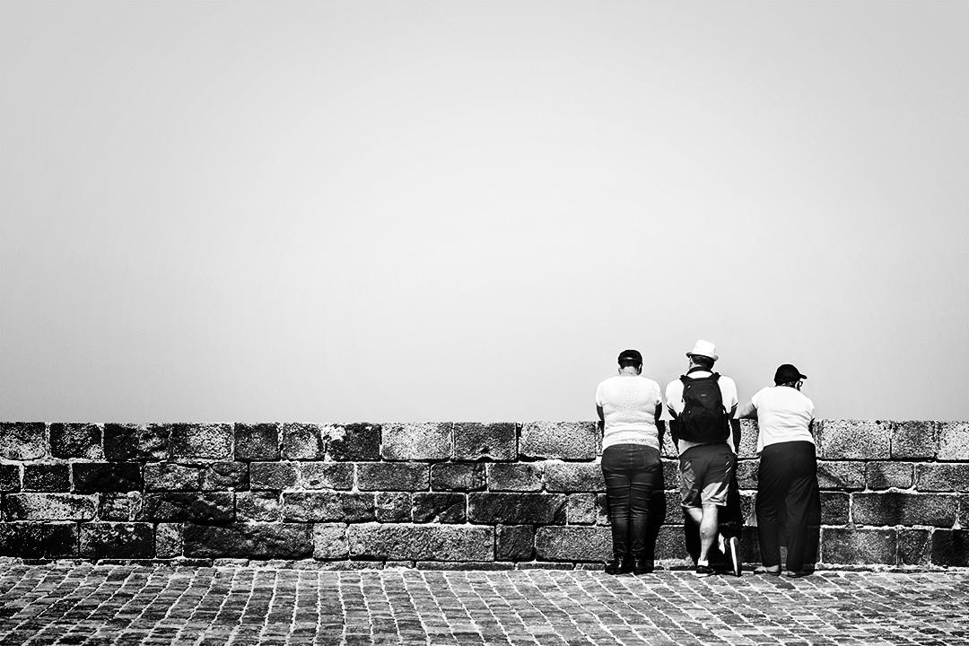 Trois personnes de dos devant un mur