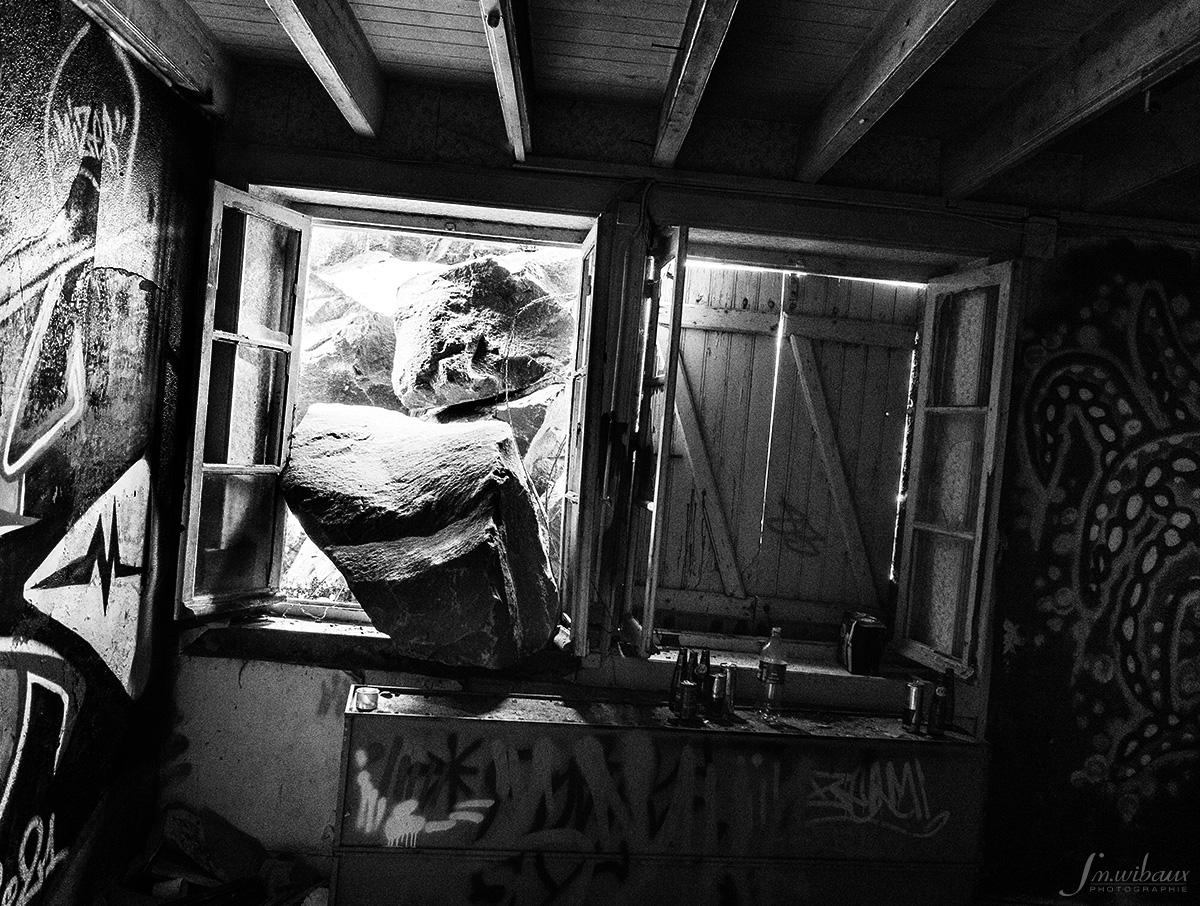 Pierres qui entrent par la fenêtre dans un bâtiment abandonné
